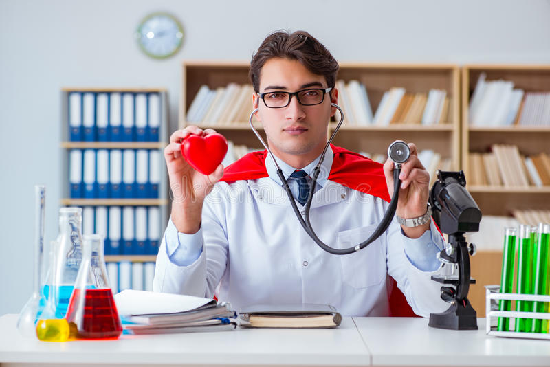 Доктор супергероя работая в лаборатории больницы стоковые фото