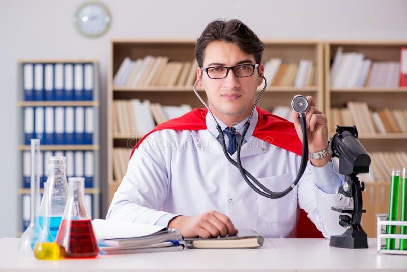 Доктор супергероя работая в больнице лаборатории стоковые изображения rf