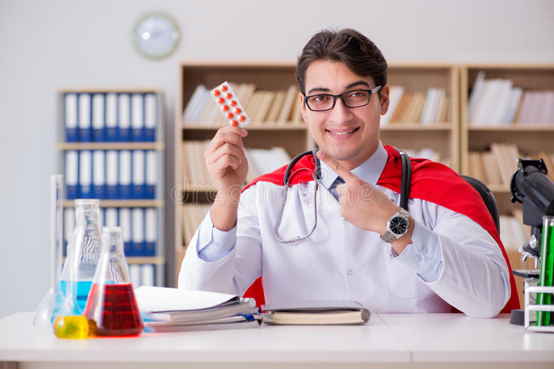 Доктор супергероя работая в больнице лаборатории стоковые фотографии rf