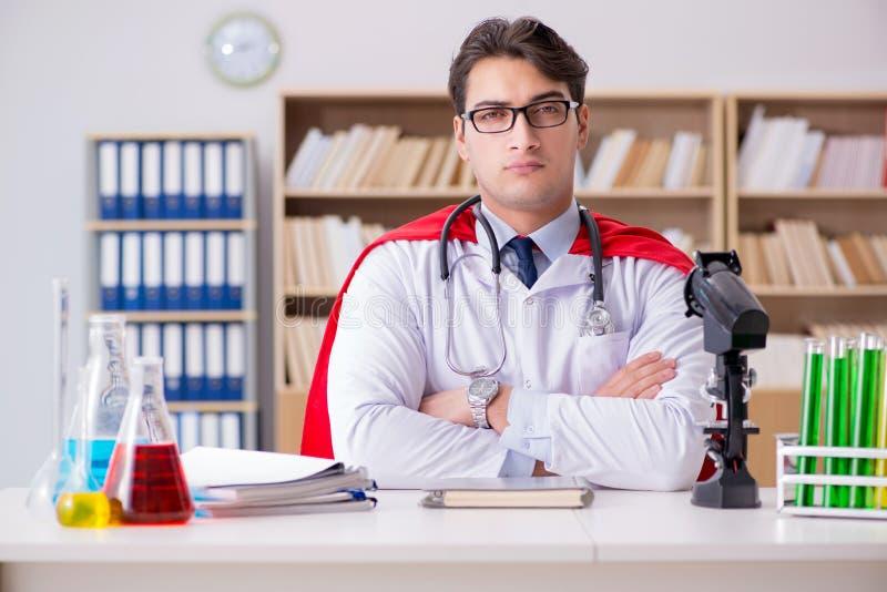 Доктор супергероя работая в больнице лаборатории стоковое фото