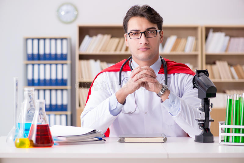 Доктор супергероя работая в больнице лаборатории стоковые изображения