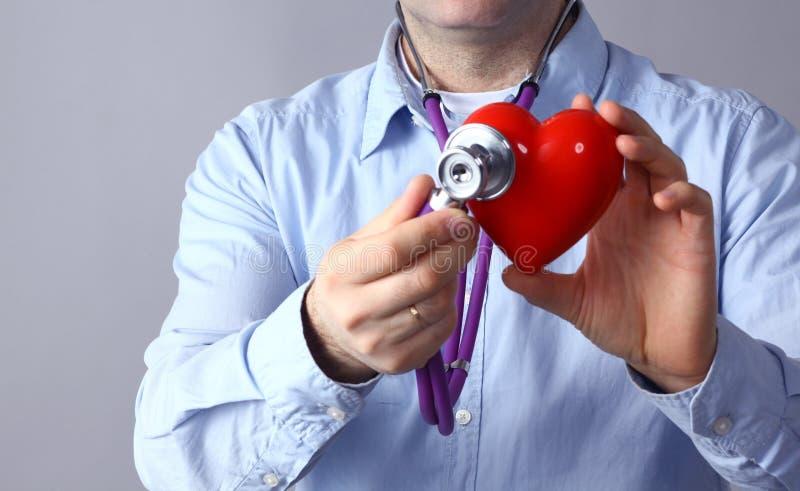 Доктор с медицинским стетоскопом рассматривая красное сердце, на серой предпосылке стоковое изображение