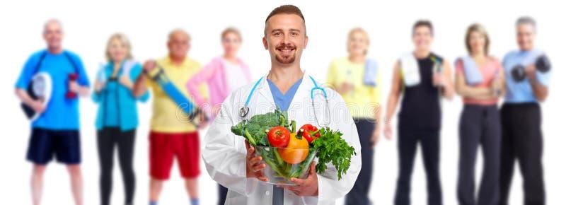 Доктор с овощами и группой в составе люди фитнеса стоковые изображения rf