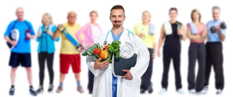 Доктор с овощами и группой в составе люди фитнеса стоковые фото