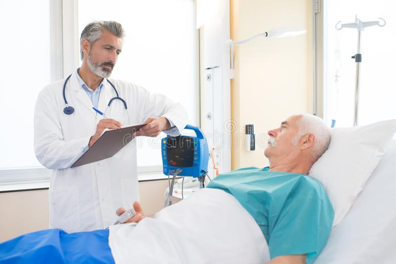 Доктор с ручкой и доской сзажимом для бумаги говоря к пациенту стоковая фотография rf