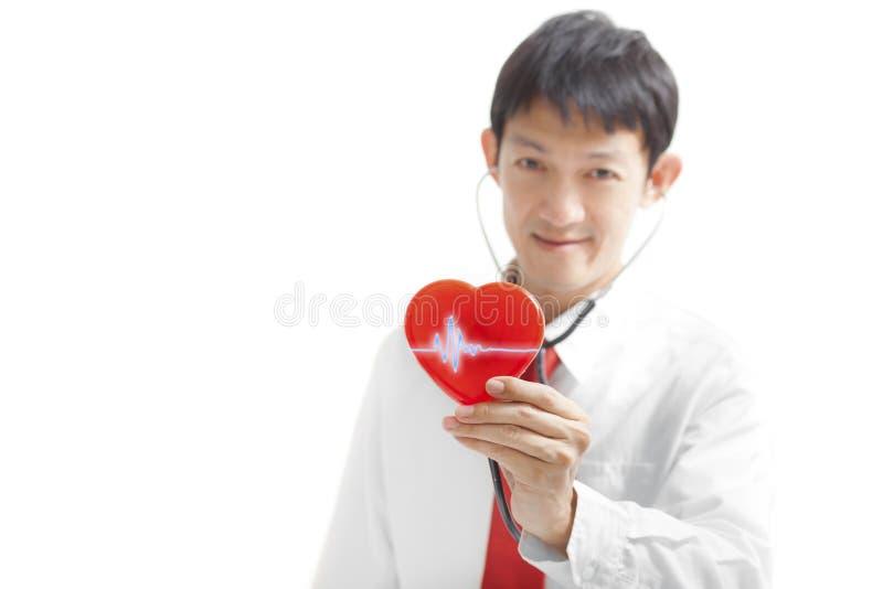 Доктор с стетоскопом рассматривая красное сердце, изолированное на сером цвете стоковая фотография rf