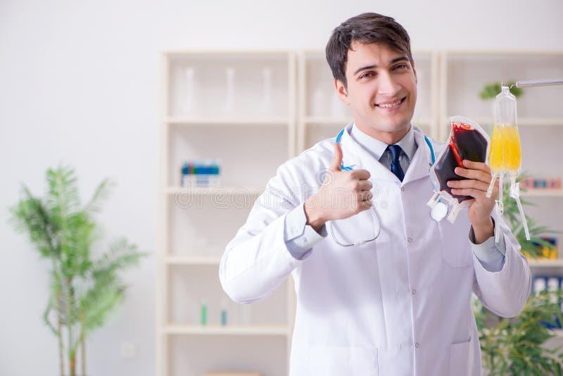 Доктор с сумкой плазмы крови в больнице стоковое фото rf