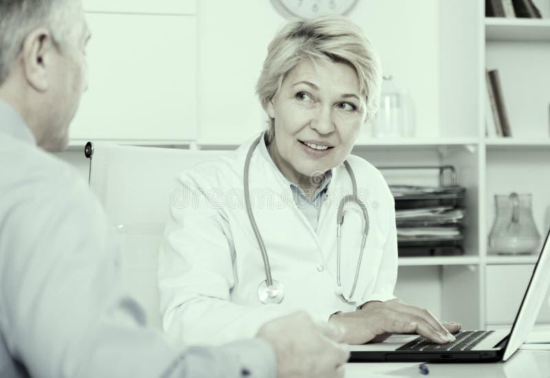 Доктор слушает к зрелому пациенту стоковое фото rf