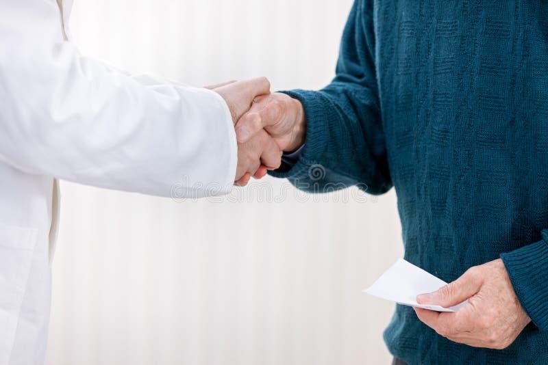 Доктор тряся с пациентом стоковая фотография