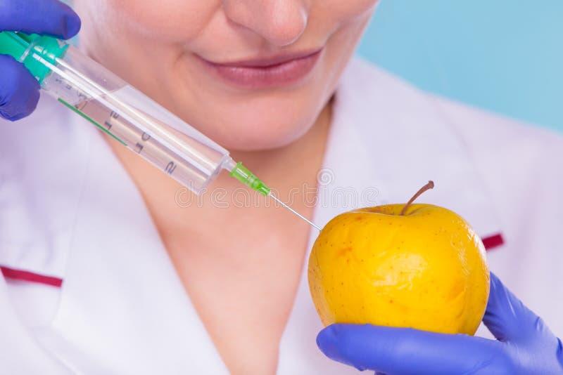 Доктор ученого впрыскивая яблоко Еда GM стоковое фото rf