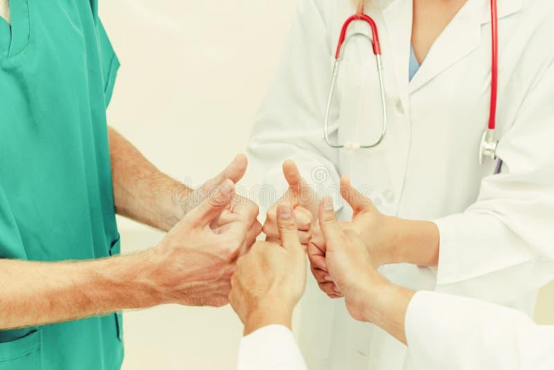 Доктор, хирург и медсестра присоединяются к рукам совместно стоковое изображение rf