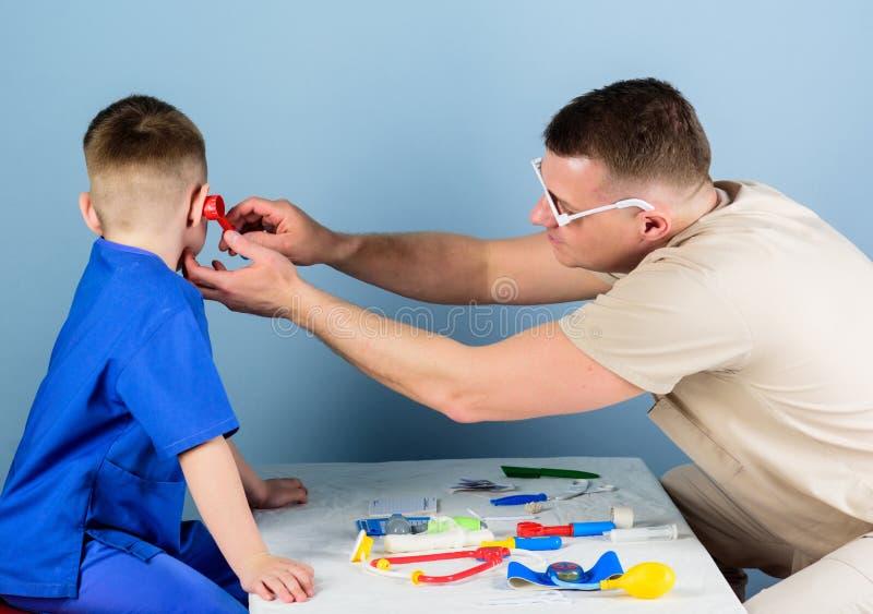 Работник больницы Медицинское обслуживание Доктор человека сидит инструменты таблицы медицинские рассматривая пациента мальчика З стоковое изображение rf