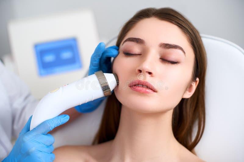 Доктор Beautician делая rf-поднимаясь процедуру для безупречной стороны женщины кладя в салон красоты Косметология оборудования стоковое фото rf