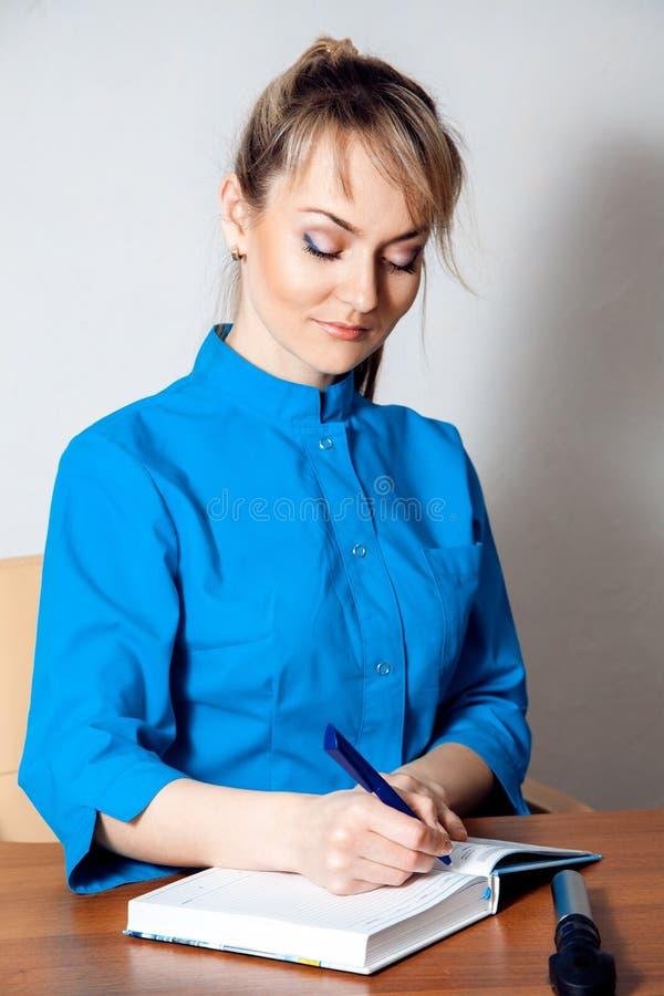 Доктор Cutie белокурый женский работая на столе стоковые фотографии rf