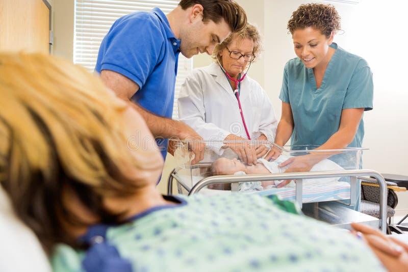 Доктор Examining Младенец Нянчить и человек с матерью стоковое изображение