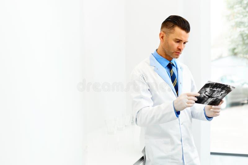 Доктор Looking дантиста на рентгеновском снимке на больнице стоковое фото