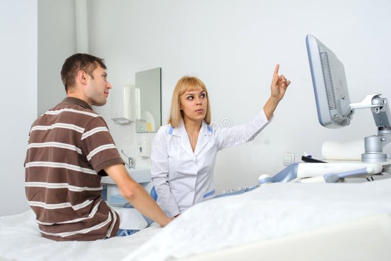 Доктор Ultrasunography объясняет прибору patientat стоковые фото