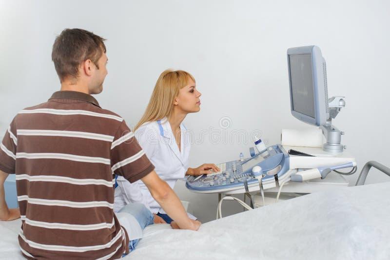 Доктор Ultrasunography объясняет прибору patientat стоковые изображения