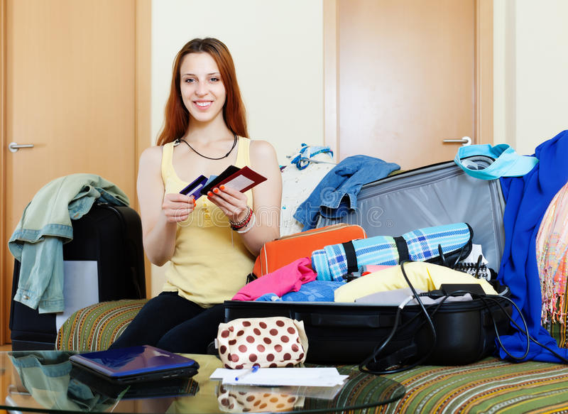 Документы упаковки молодой женщины в чемоданы стоковые изображения
