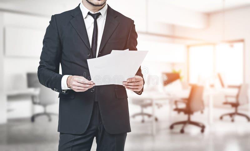 Документы чтения бизнесмена в офисе стоковое фото