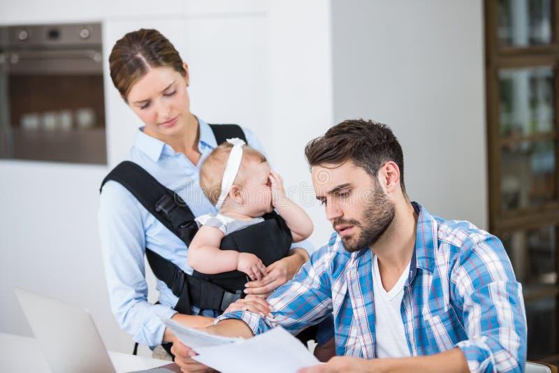 Документы чтения человека пока младенец нося жены стоковые изображения rf
