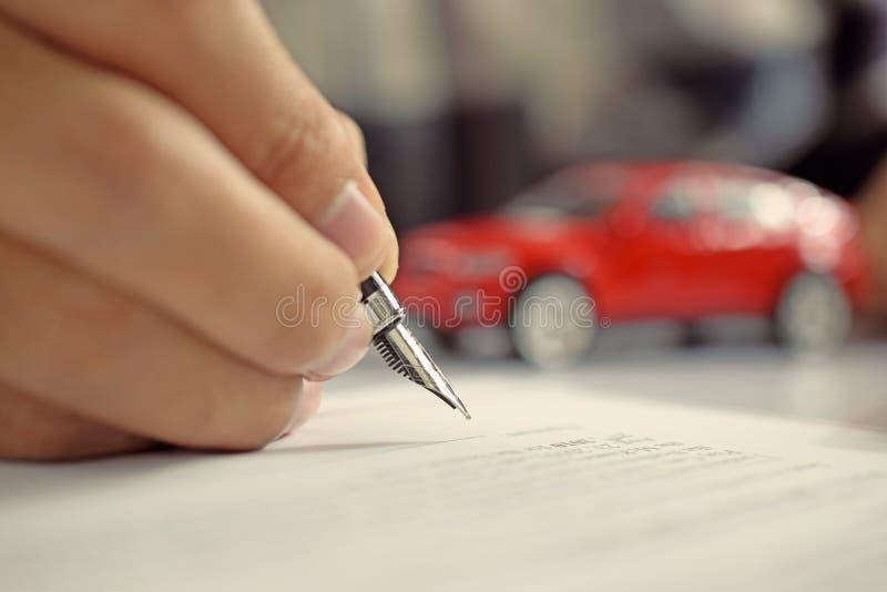 Документ страхования автомобилей подписания человека Подпись сочинительства на contrac стоковые фотографии rf