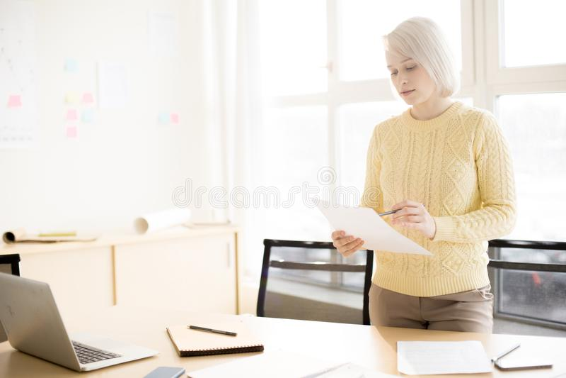 Документ чтения женщины в офисе стоковые фото