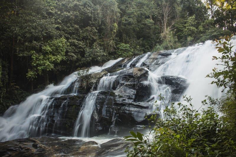 Долгая выдержка благоговени-воодушевляя водопада окруженная зеленой вегетацией в лесе Чиангмае Mae Klang Luang, Таиланде стоковые изображения rf