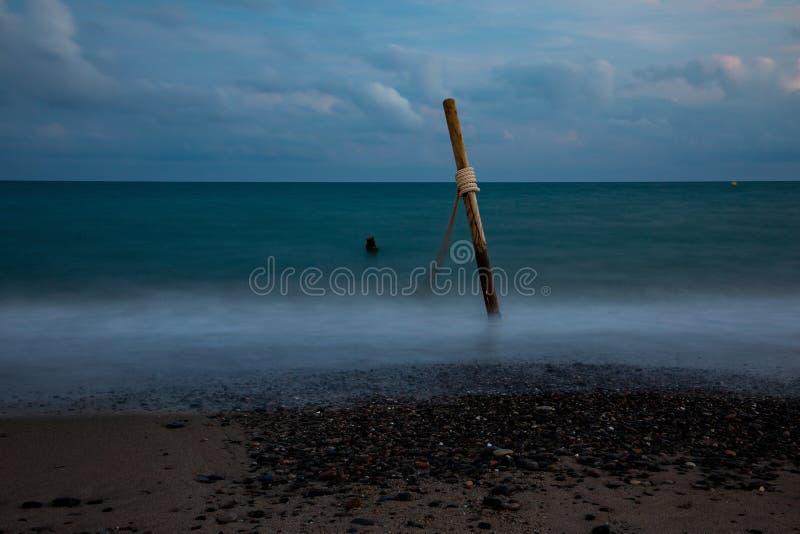Долгая выдержка морской воды с деревянными журналами и веревочкой, на облачном небе стоковые фотографии rf