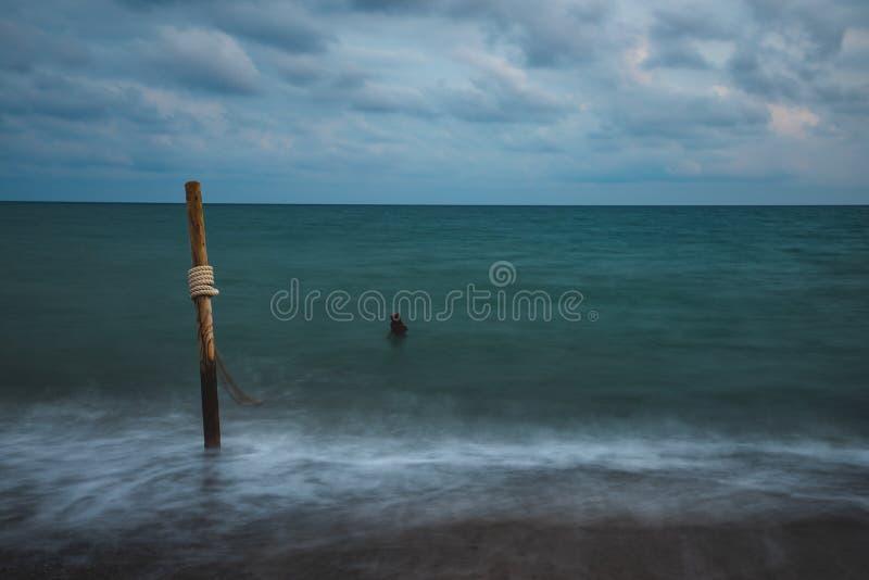 Долгая выдержка морской воды с деревянными журналами и веревочкой, на облачном небе стоковое фото rf