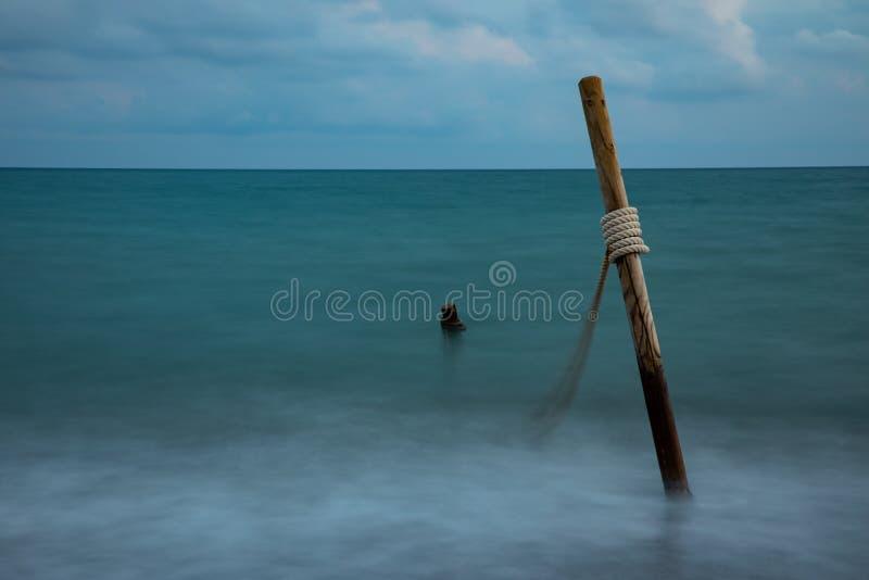 Долгая выдержка морской воды с деревянными журналами и веревочкой, на облачном небе стоковое изображение