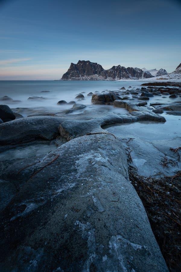 Долгая выдержка на пляже Utakliev во время захода солнца в Норвегии, островах Lofoten стоковые изображения rf