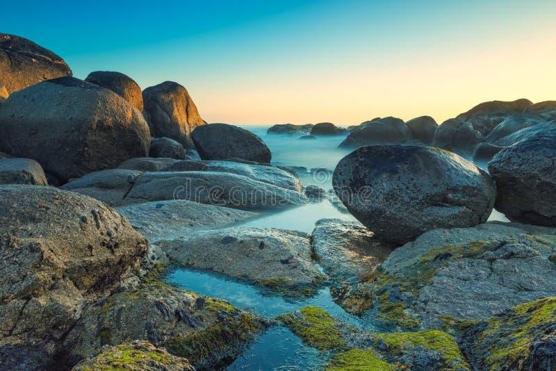 Долгая выдержка снятая океана среди утесов на пляже Низкая точка зрения стоковые изображения rf