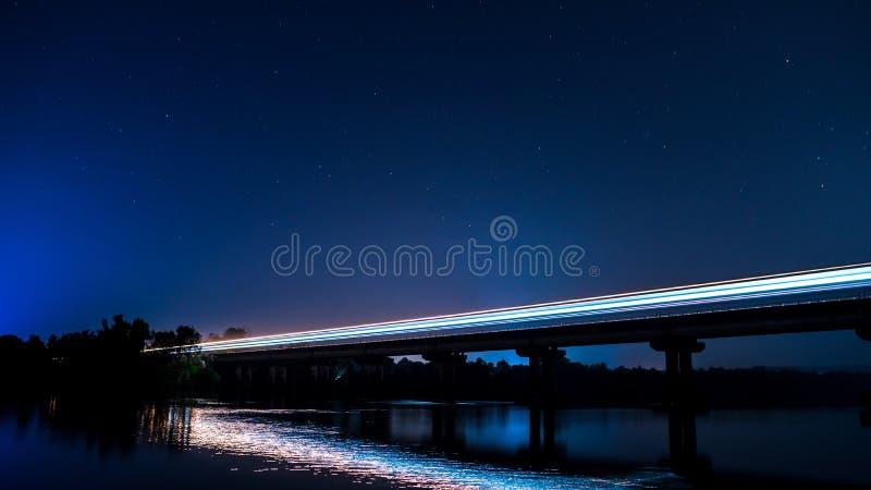Долгая выдержка снятая поезда на мосте вечером стоковая фотография rf