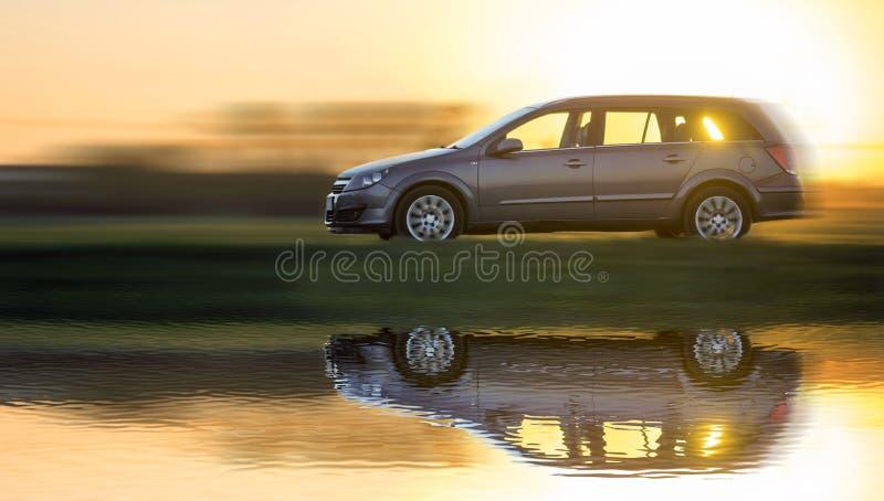 Долгая выдержка снятая серого серебряного автомобиля двигая быстро в сельскую местность на запачканном ярком оранжевом ясном небе стоковое изображение