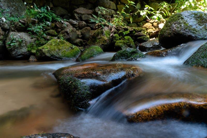 Долгая выдержка снятая чистой воды пропуская через большие утесы 1 стоковое фото