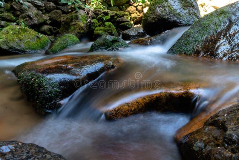 Долгая выдержка снятая чистой воды пропуская через большие утесы 2 стоковая фотография