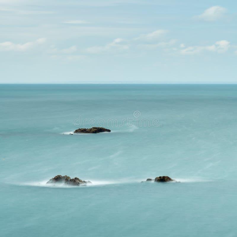 Долгая выдержка 3 утесов в светлом - голубое море стоковое изображение rf
