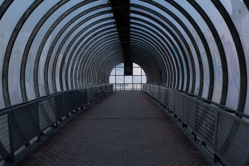 Долгий пешеходный туннель с металлическими арками и стеклянным дизайном Воздушный пешеходный переход через дорогу, темно-пустой т стоковое изображение rf