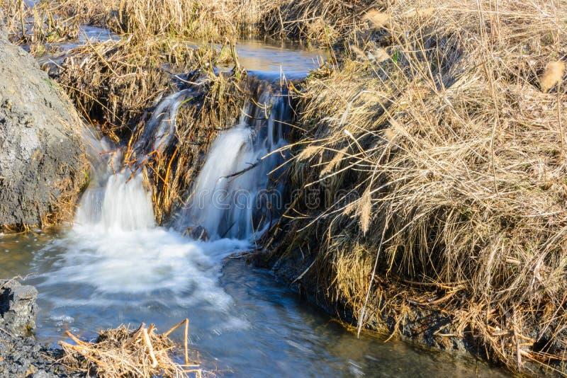 Долгожданная подача заводей весны над промоинами и холмами на солнечный день Речные пороги воды и водопады потоков среди сухой тр стоковое изображение rf