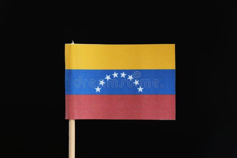 Должностное лицо и первоначальный флаг Венесуэлы на зубочистке на черной предпосылке Горизонтальное tricolor желтого, голубого и  стоковая фотография rf