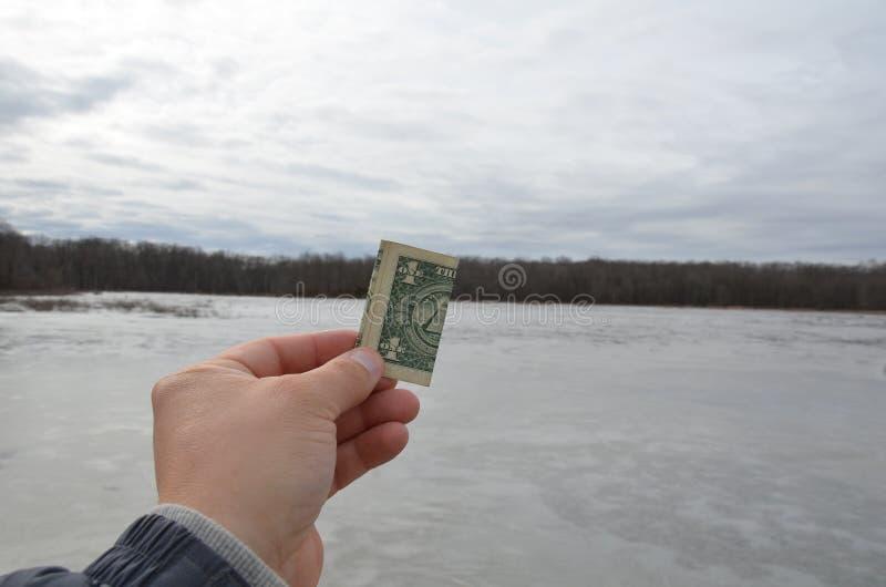 Долларовая банкнота удерживания одного руки в области заболоченного места с замороженной водой стоковые фотографии rf