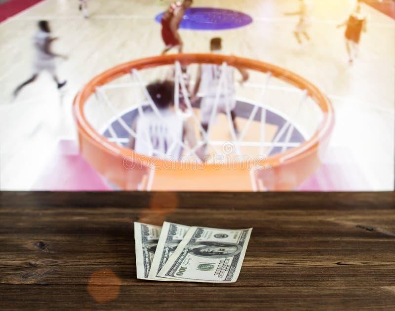 Доллары денег на деревянной предпосылке на предпосылке ТВ показывая баскетбол стоковая фотография rf