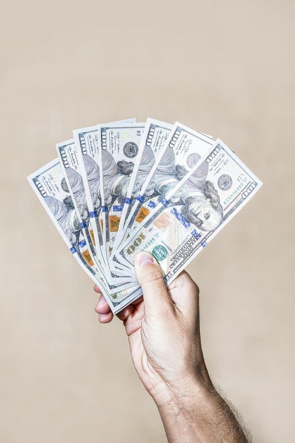 Доллары дуют счеты 100 долларов в руке стоковая фотография
