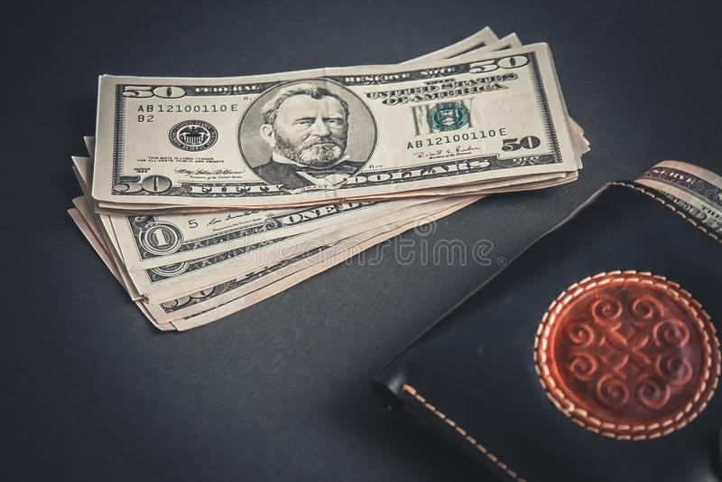 Доллары и бумажник на черном поле стоковые изображения rf