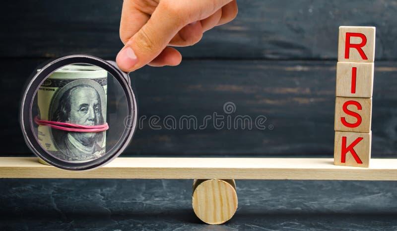 """Доллары и надпись """"риск """"в масштабах Концепция финансового риска и инвестировать в проекте дела Делать ri стоковое фото"""