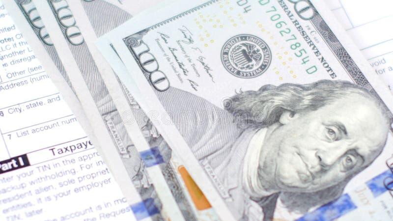 Доллары падая на налоговую форму стоковая фотография