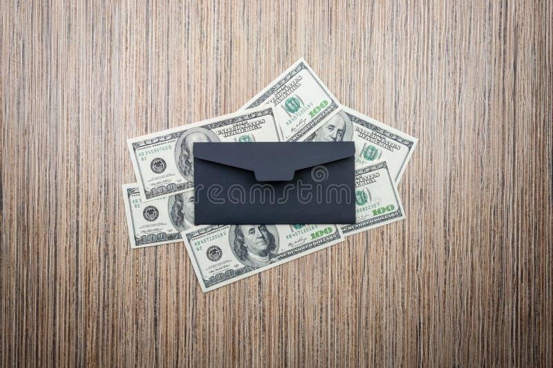 Доллары с черным конвертом на деревянном столе Взгляд сверху стоковые фотографии rf