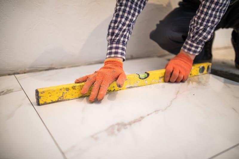 Домашнее улучшение плитки - разнорабочий при уровень кладя вниз с плиточного пола дома стоковое фото