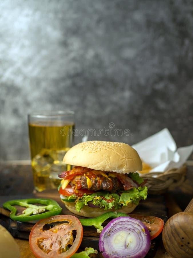 Домашние бургеры с пивом и колой из бекона, свинины, помидора, салата, лука, сыра и специй на деревянном фоне стоковое фото
